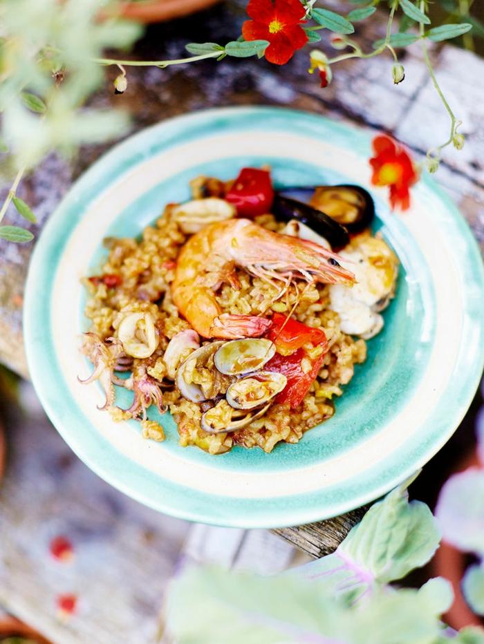 abendessen inspiration paella mit meeresfrüchten reisgerichte ideen spanische gerichte zubereiten rote blume große garnelle