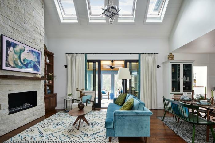 attraktives blaues sofa grüne kissen weiße backsteinwand bunter teppich ovaler kaffeetisch velux austauschfenster abstraktes gemälde