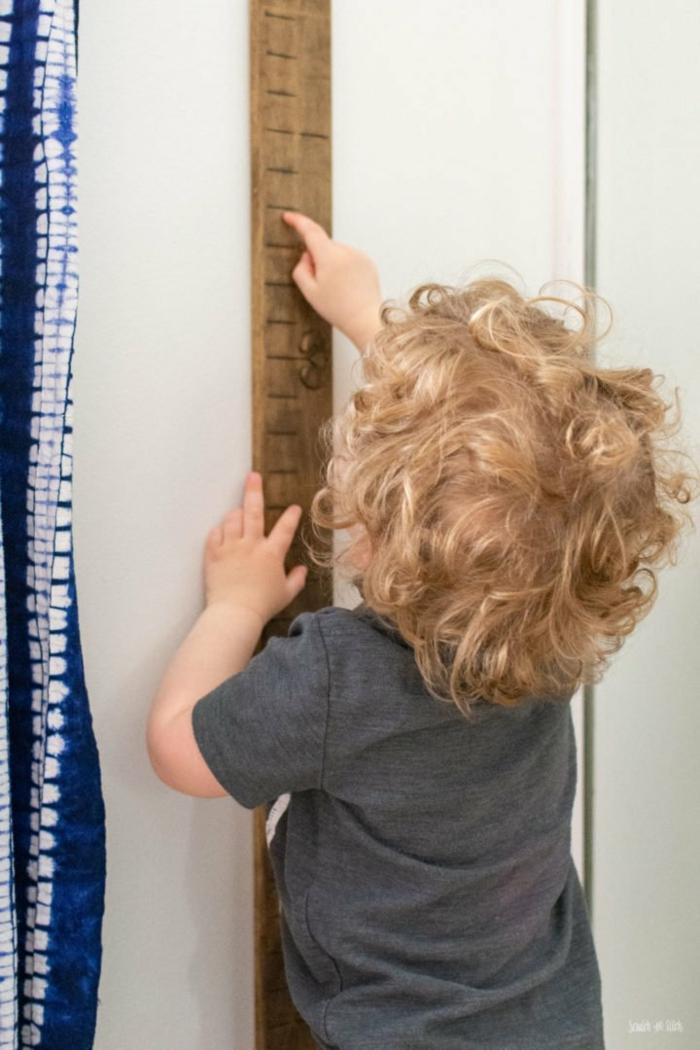 blondes kind im grauen t shirt kinderzimmer deko messlatte für kinder aus holz selber machen deko ideen