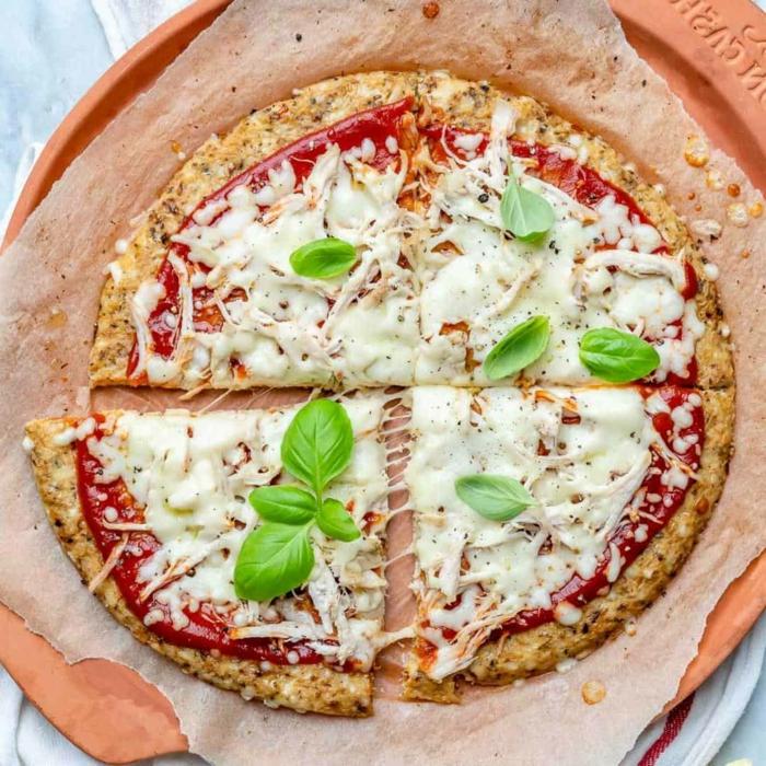 blumenkohl rezepte eine blumenkohl pizza mit basilikum blättern und käse und tomaten