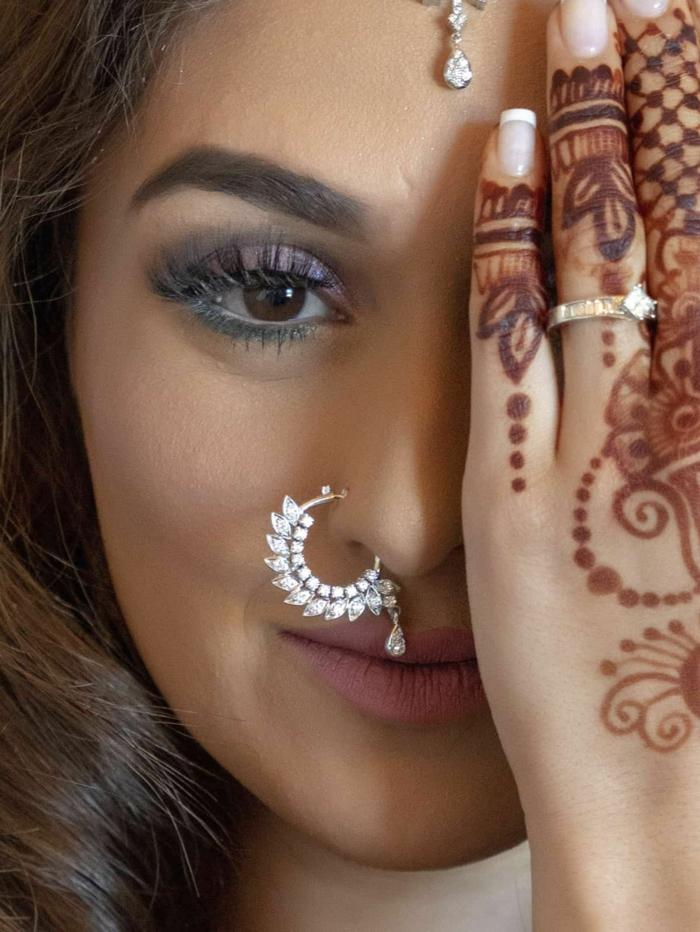 braune augen henna tattoo auf der hand frau mit braunen haare großes nasenring piercing indische kultur inspo