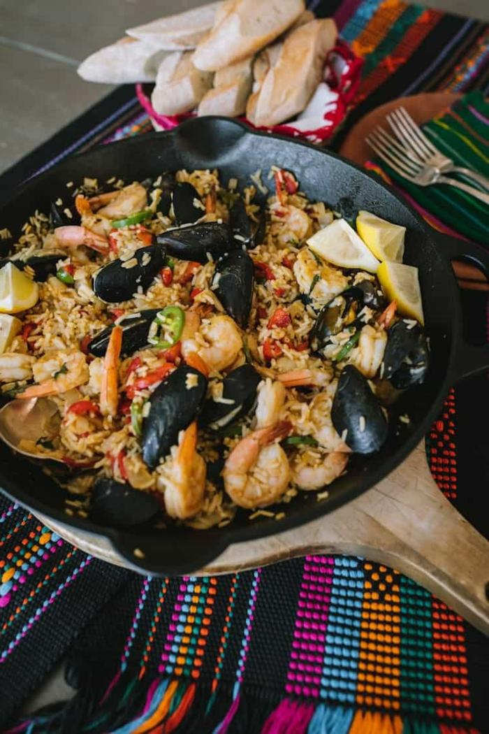 bunte tischdecke paella mit meeresfrüchten garnellen und miesmuscheln reisgerichte spanisch ideen abendessen kochen teller mit brot