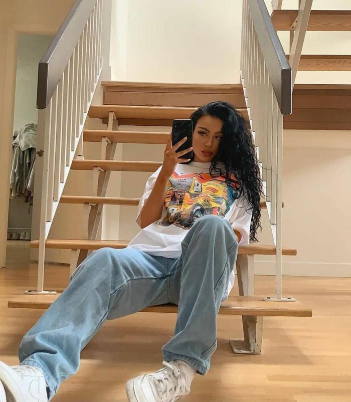 casual outfit oversized outfit weite jeans t shirt mit print weiße sneakers dame mit langen schwarzen haaren baddie outfits