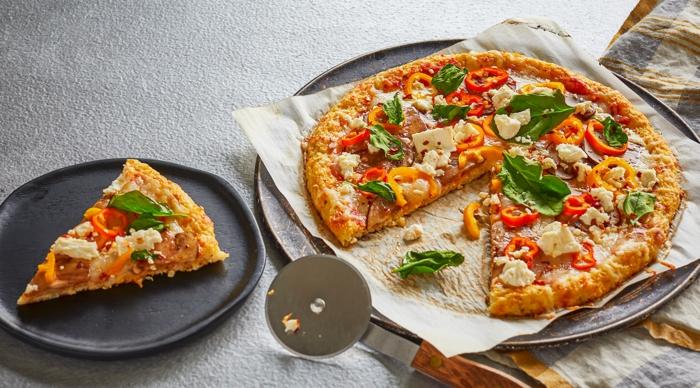 ein grauer teller mit einem stück pizza mit blumenkohl und basilikum und frischen tomaten