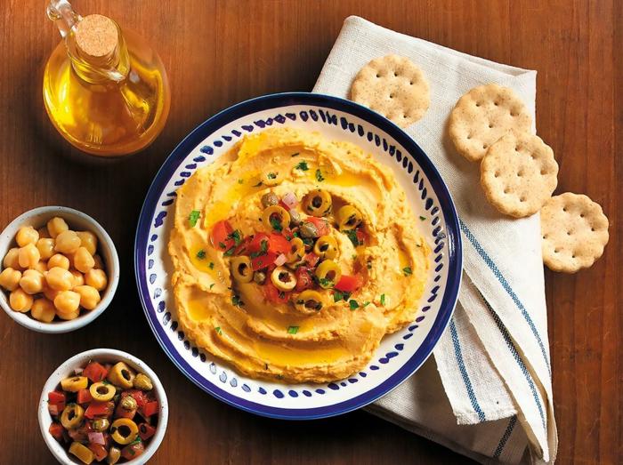 eine flasche mit olivenöl hummus selber machen rezept brot und eine weiße decke