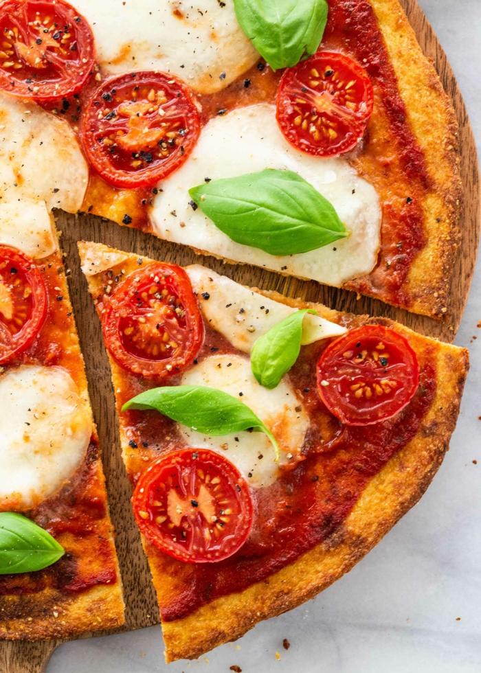 eine pizza mit tomaten und blumenkohl und frischen basilikum blättern