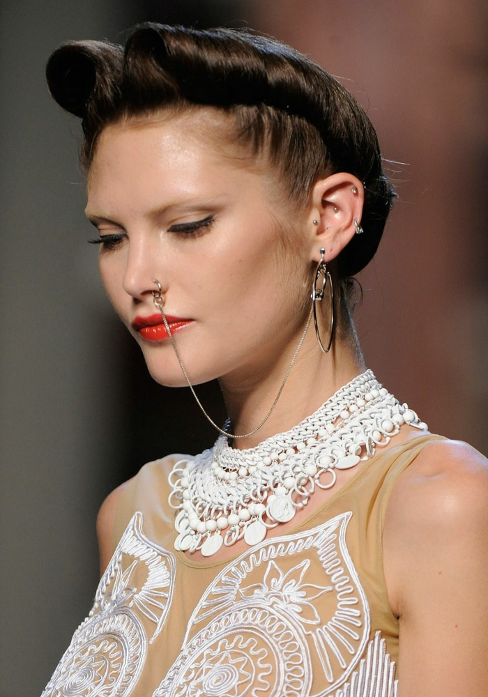 fashion week show elegantes kleid mit spitze model mit braunen haaren roter lippenstift nasenring gold mit kette viele ohrringe