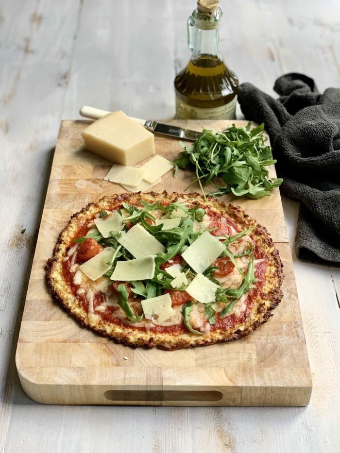 flasche mit olienöl ein holzbrett und eine pizza mit käse und blumenkohl