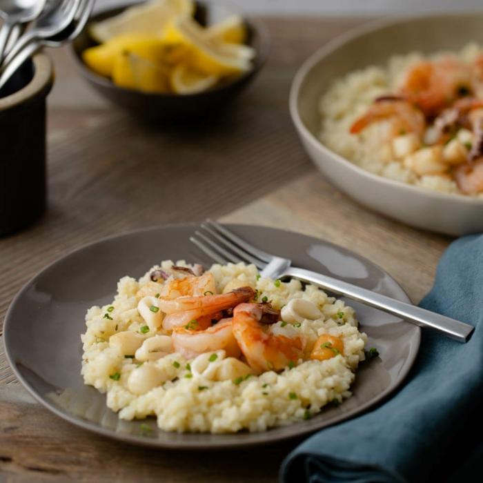 gabel ein grauer teller mit blumenkohl risotto mit garnelen gerichte mit blumenkohl