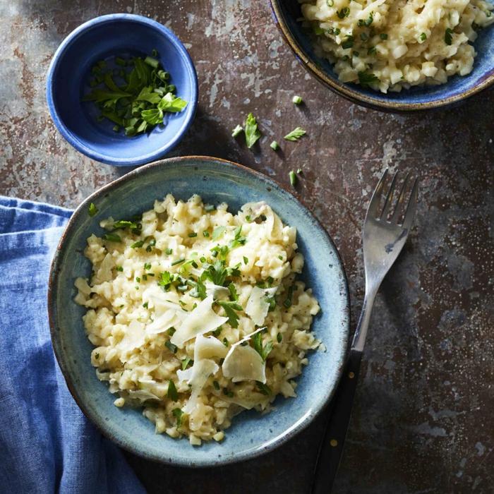 gabel und ein teller mit weißem reis blumenkohl risotto mit petersilie