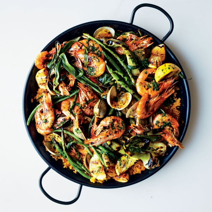 gesunde ernährung essen spanische reisspeise mit gemüse und meeresefrüchten schwarze pfanne