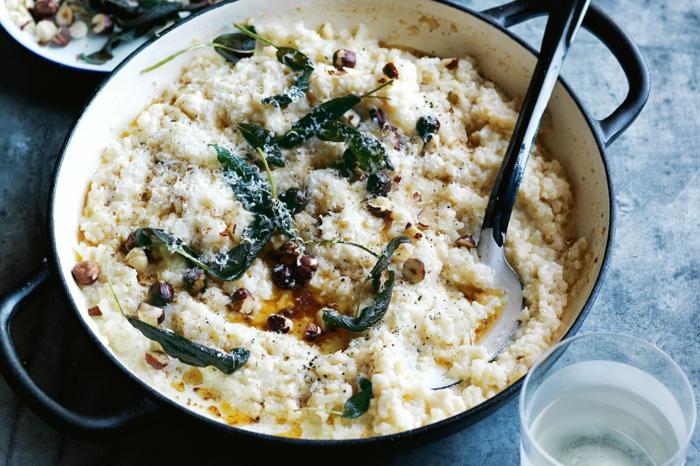 glas mit wasser eine pfanne mit reis ein löffel blumenkohl risotto mit petersilie