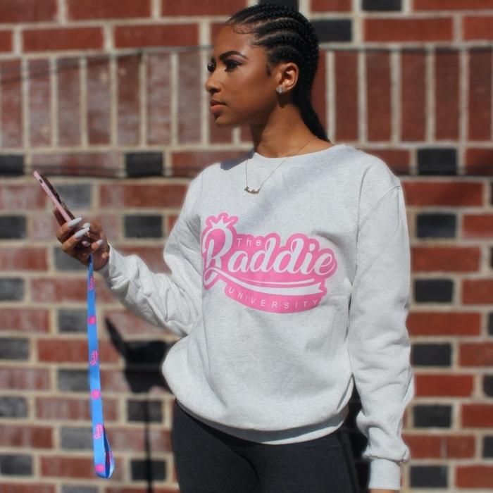 graues sweatshirt mit print baddie aesthetic outfits schwarze hosen lange haare mit zöpfen frau hält handy in der hand