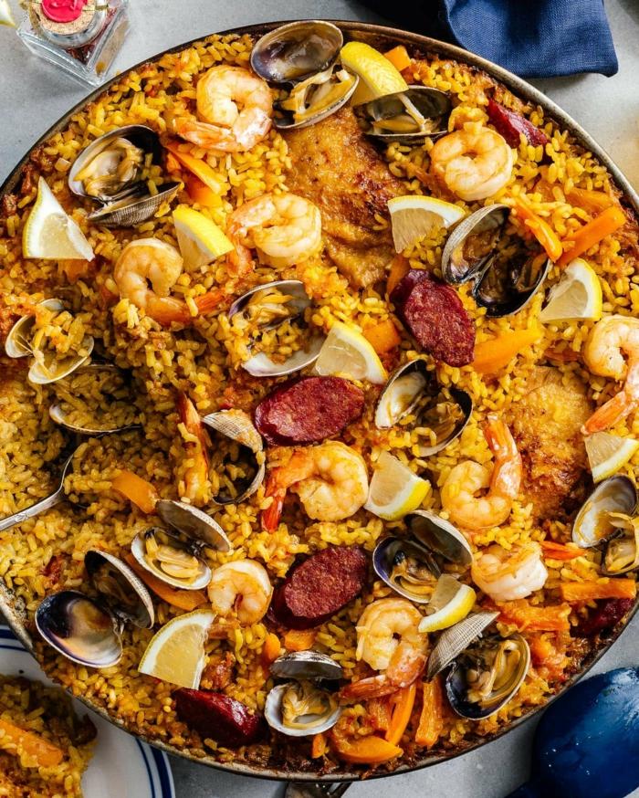 große schale spanische reisespeise leckere paella rezepte inspiration reis mit meeresfrüchten und fleisch zitronen
