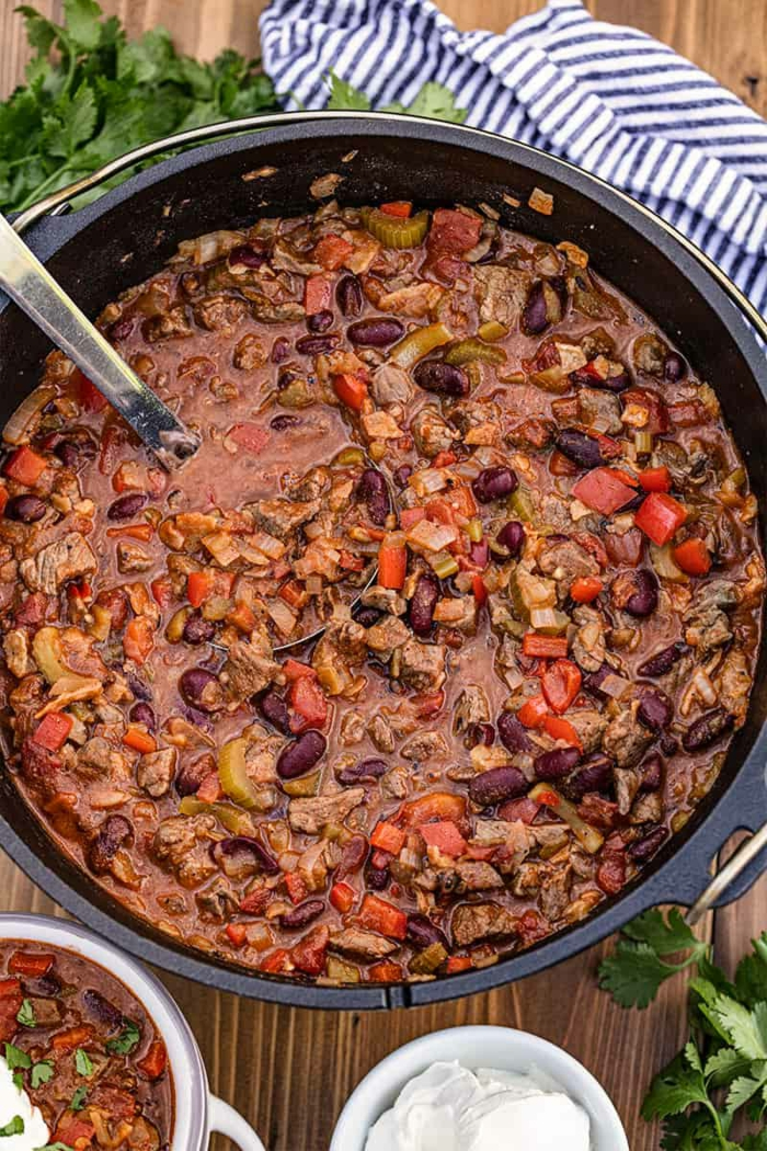 großer schwarzer topf chili rezepte dutch oven gerichte für die ganze familie blau weißes tuch parsley