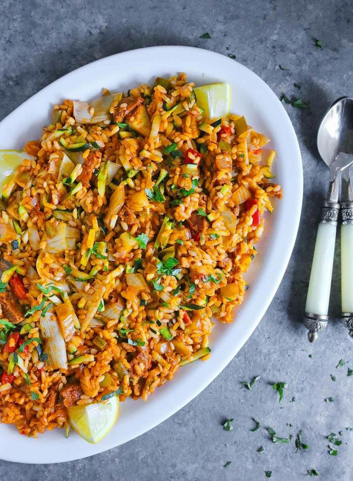 großer weißer teller vegetarische paella rezept original mit gemüse weißer löffel gesunde ernährung koche ideen abendessen