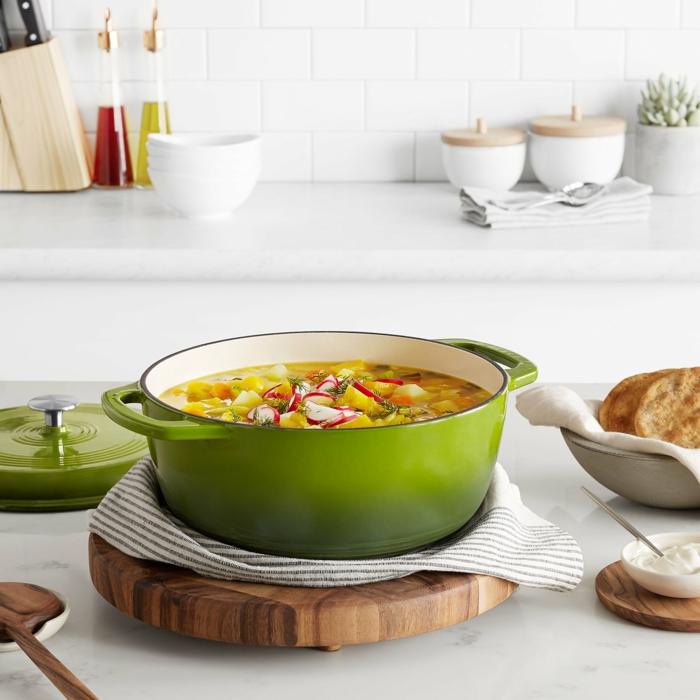großes grüner topf auf schneidebrett aus holz dutch oven gerichte mit gemüse weiße küchentheke