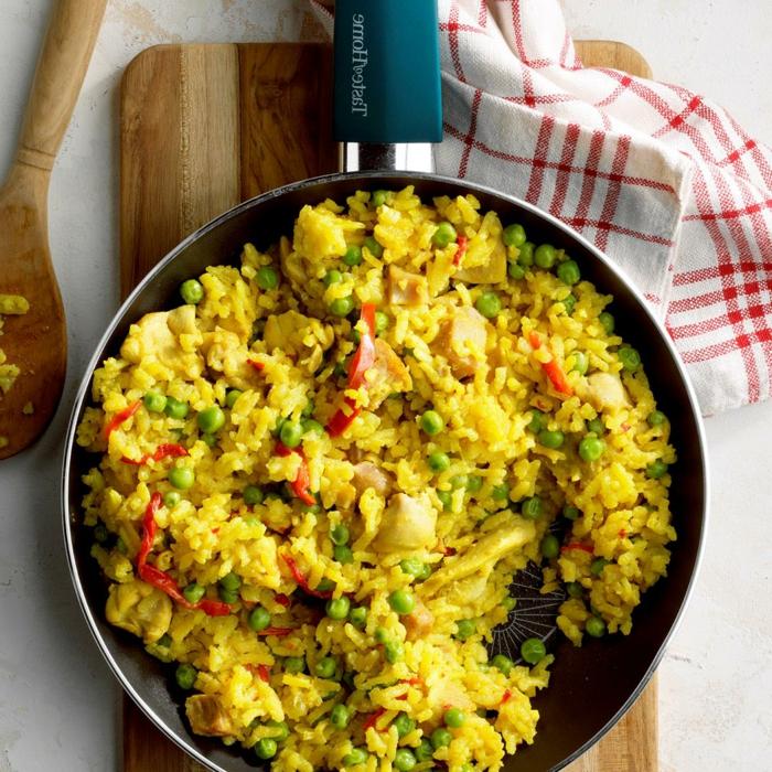 hänchen paella reis mit gemüse und fleisch spanisch style kochen rotes küchentuch mit roten streifen holzbrett und löffel