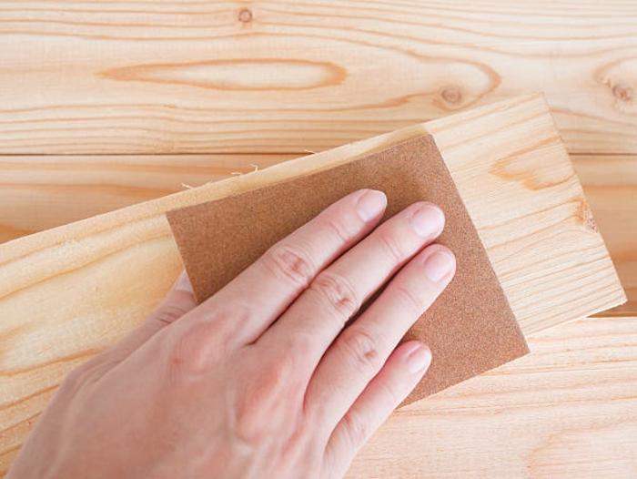eine hand mit schleifpapier
