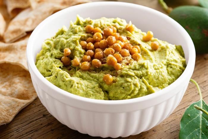 hummus selber machen rezept eine weiße schüssel mit hummus mit kichererbsen und avocado