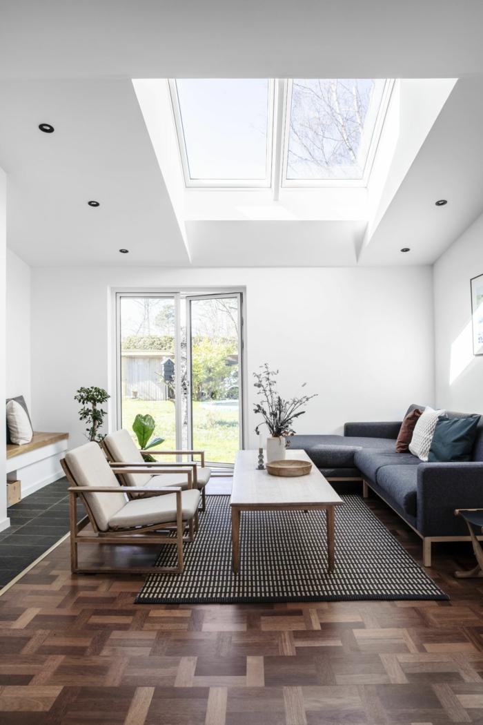 klassische einrichtung wohnzimmer holz akzente velux fenster einbauen schwarzer ecksofa vase mit blumen holzsessel weiße polsterung