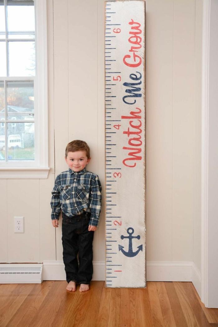 kleines kind im karierten hemd schwarze hosen messlatte personalisiert blauer anker jungenzimmer deko