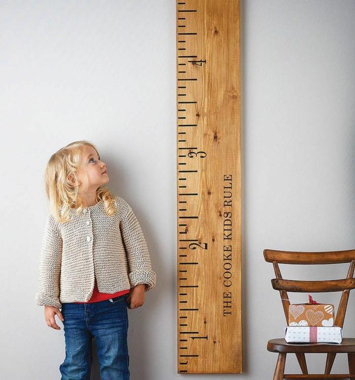 kleines kind mit blonden haaren kleiner stuhl aus holz dekoration messlatte kinderzimmer inspiration und ideen