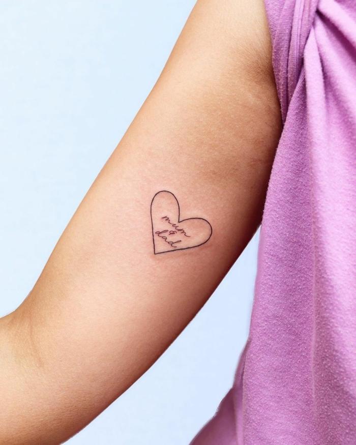 kleines minimalistisches mama papa tattoo am arm in einem herz lila t shirt