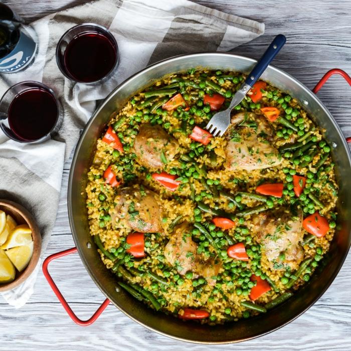 kochen 2021 hähnchen paella mit kichererbsen blaue gabel zwei gläser mit wein spanische gerichte mit reis