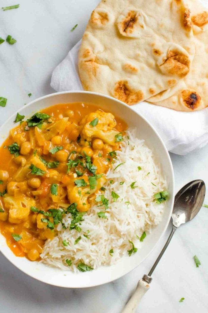 löffel ein brot ein teller mit weißem reis ein gericht mit blumenkohl curry