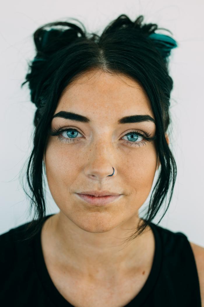 lange hochgesteckte schwarze haare langhaarfrisuren frau mit blauen augen schwarzes top nasenring piercing nostril schwarz