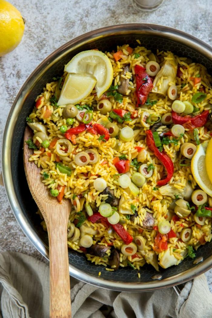 leckere rezepte abendessen ideen paella reis mit gemüse und oliven großer löffel aus holz klassische speisen spanien