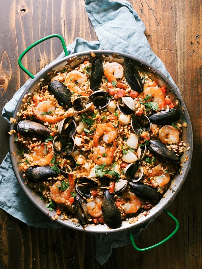 miesmuscheln und garnellen würzige meeresfrüchte paella reis gericht spanische küche traditionell blaues tusch tisch aus holz