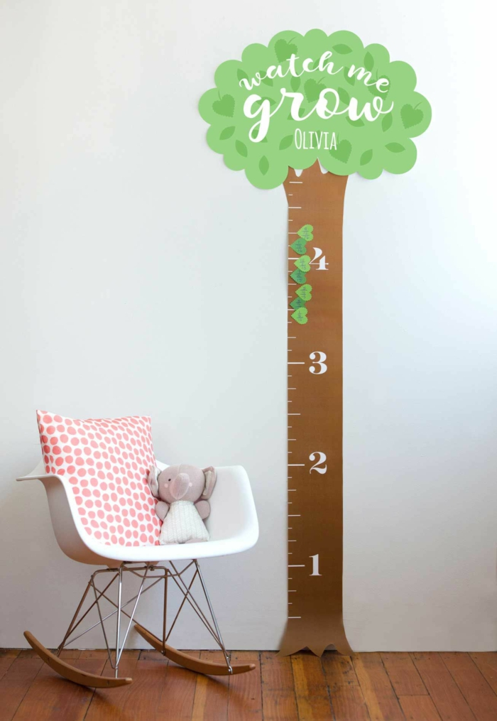 minimalistischer stuhl scandi style weißes kissen mit roten punkten messlatte kinderzimmer wandsticker baum mit grüner krone kuscheltier elefant
