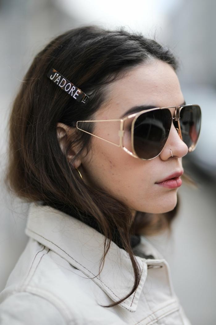 moderne schwarze sonnenbrillen braune haare dame nasenring gold elegante haarnadel street style inspiration weiße jeansjacke