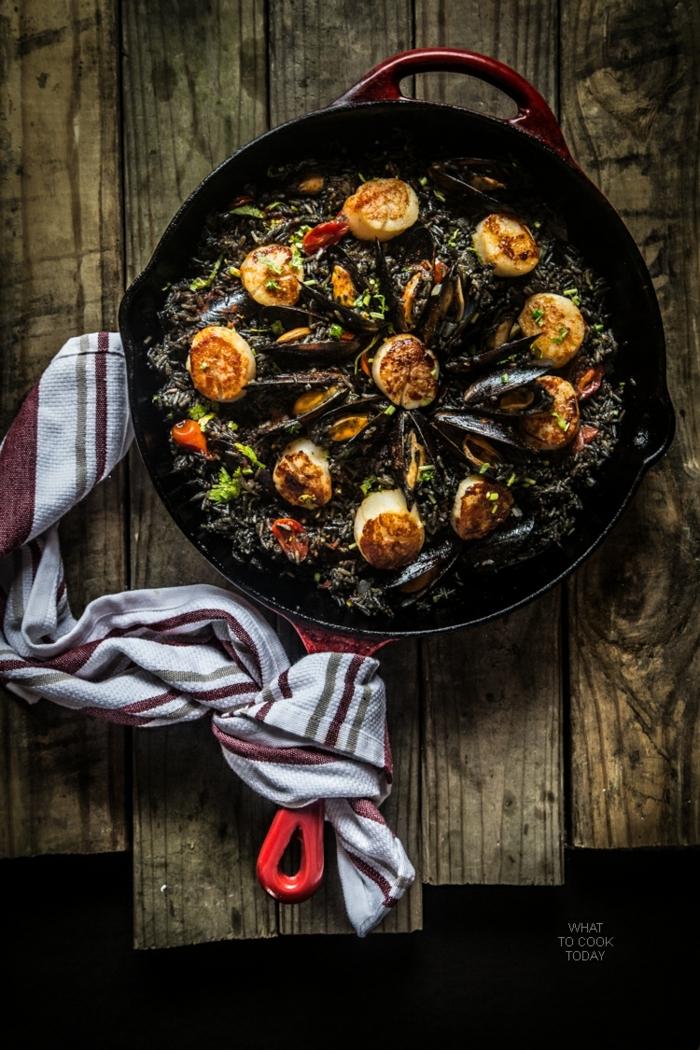 originelle abendessen ideen paella mit meeresfrüchten ideen holztisch weißes küchentuch kochen ideen rote pfanne
