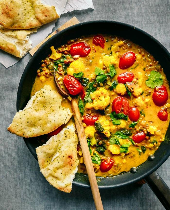 pfanne mit einem gericht mit blumenkohl ein blumenkohl curry und ein löffel aus holz