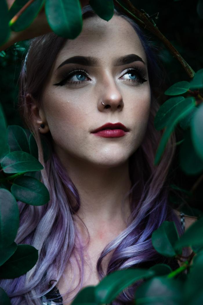 romantisches fotoshooting model mit lila haare gewellt roter lippenstift katzenaugen make up nasenpiercing nostril ideen grüne pflanzen