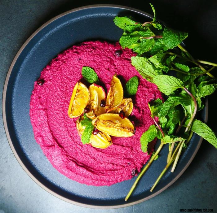 rote beete hummus selber machen rezept mit basilikum blätter und zitronen ein blauer teller mit hummus