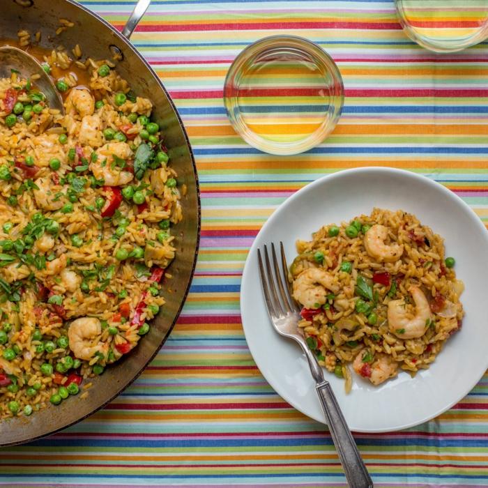 scampi garnellen paella rezept original mit meeresfrüchten bunte tischdecke weißer teller mit speise