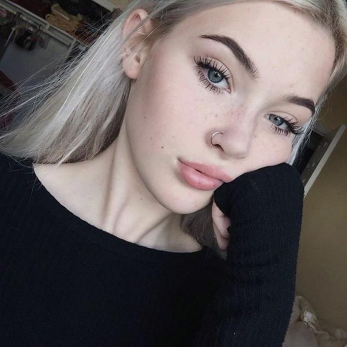 schwarze bluse casual outfit lange blonde haare hand im gesicht natürliches make up nasenring gold inspo ideen information nasenpiercings