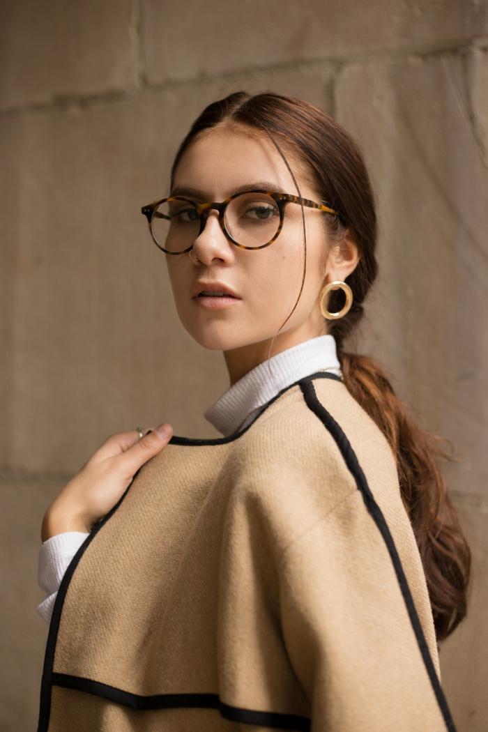 stylish gekleidete frau hellbrauner poncho lange braune haare runde brillen nasenpiercing nostril inspo