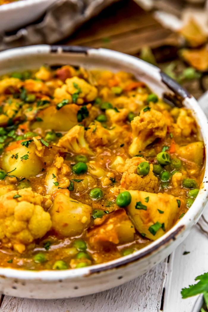 tisch aus holz ein teller mit einem blumenkohl curry mit petersilie und kurkuma