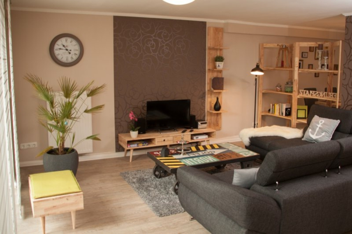 was ist souterrain kellerwohnung souterrain bedeutung wohnzimmer großes sofa grau buchregal aus holz fenster pflanzen