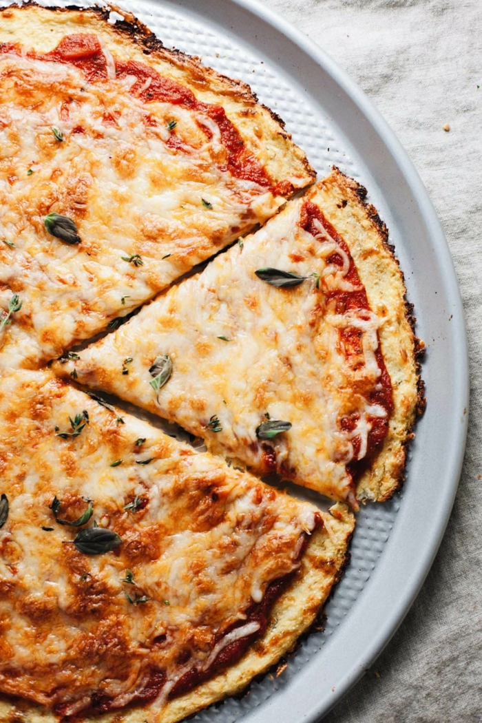 weißer teller mit blumenkohl pizza mit tomaten und champignons
