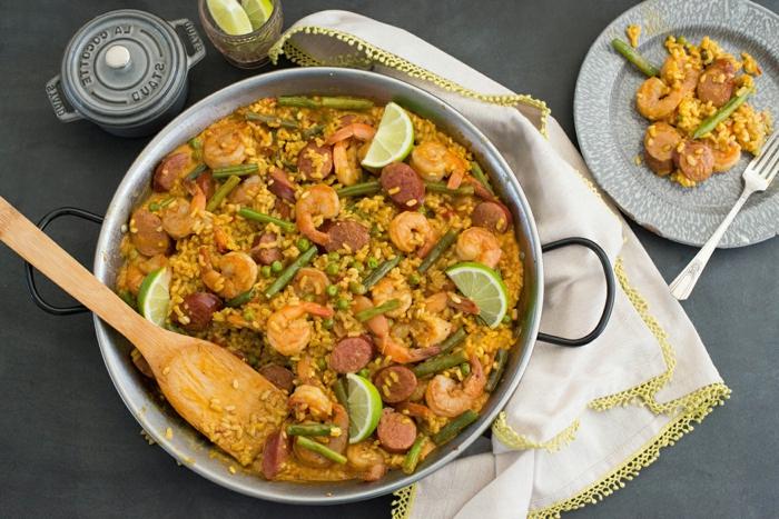 weißes küchentuch teller mit speise mallorquinische paella rezept traditionell glas mit zitronen