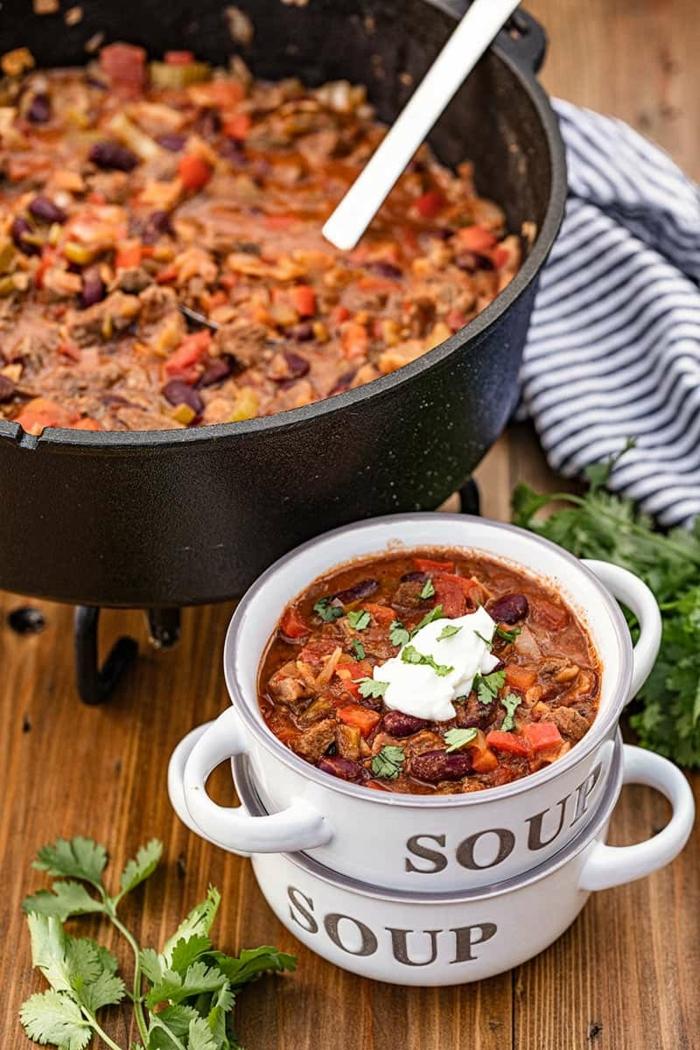 zwei kleine schalen mit chili rezepte dutch oven großer schwarzer topf tisch aus holz leckere speise