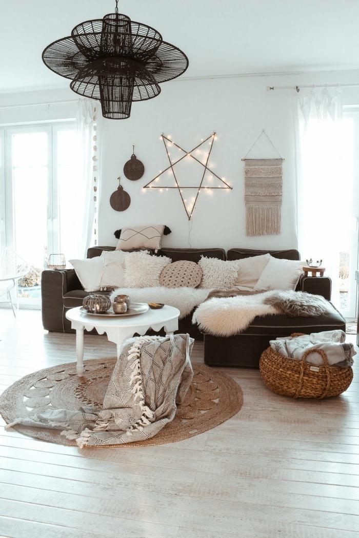 2021 interior design gemütliches wohnzimmer modern einrichten im hygge style skandinavische inspiration innenausstattung viele deko kissen stern wandlampe schwarzes ecksofa