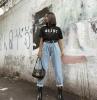 ac dc t shirt schwarz klassisches outfit street style hellblaue jeans damen slouchy style schwarze boots und tasche dame mit kurzen haaren