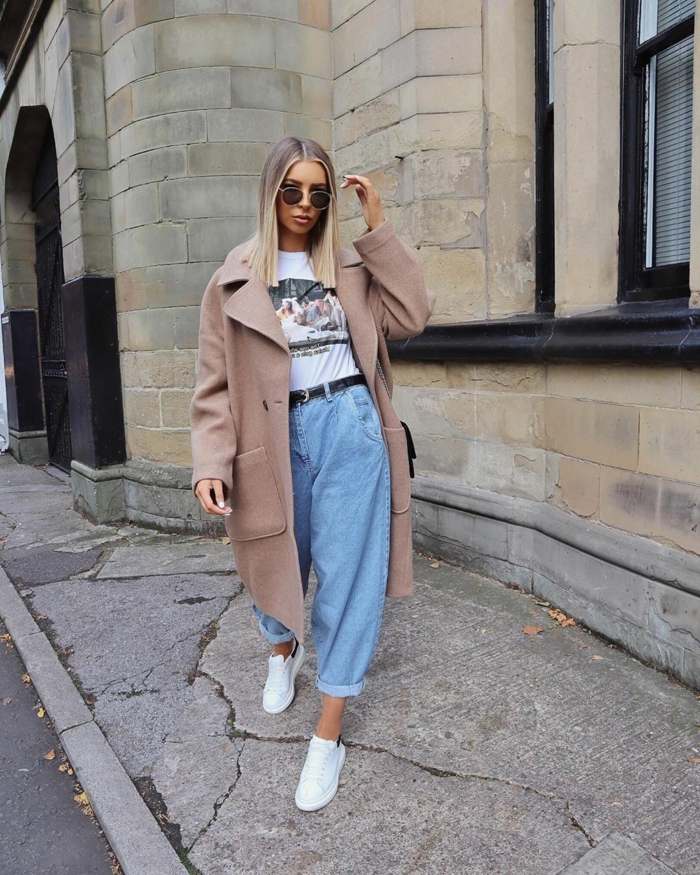 beiger oversized mantel mit weiten jeans slouchy hose gestylt mit weißen sneakers und t shirt blonde frau